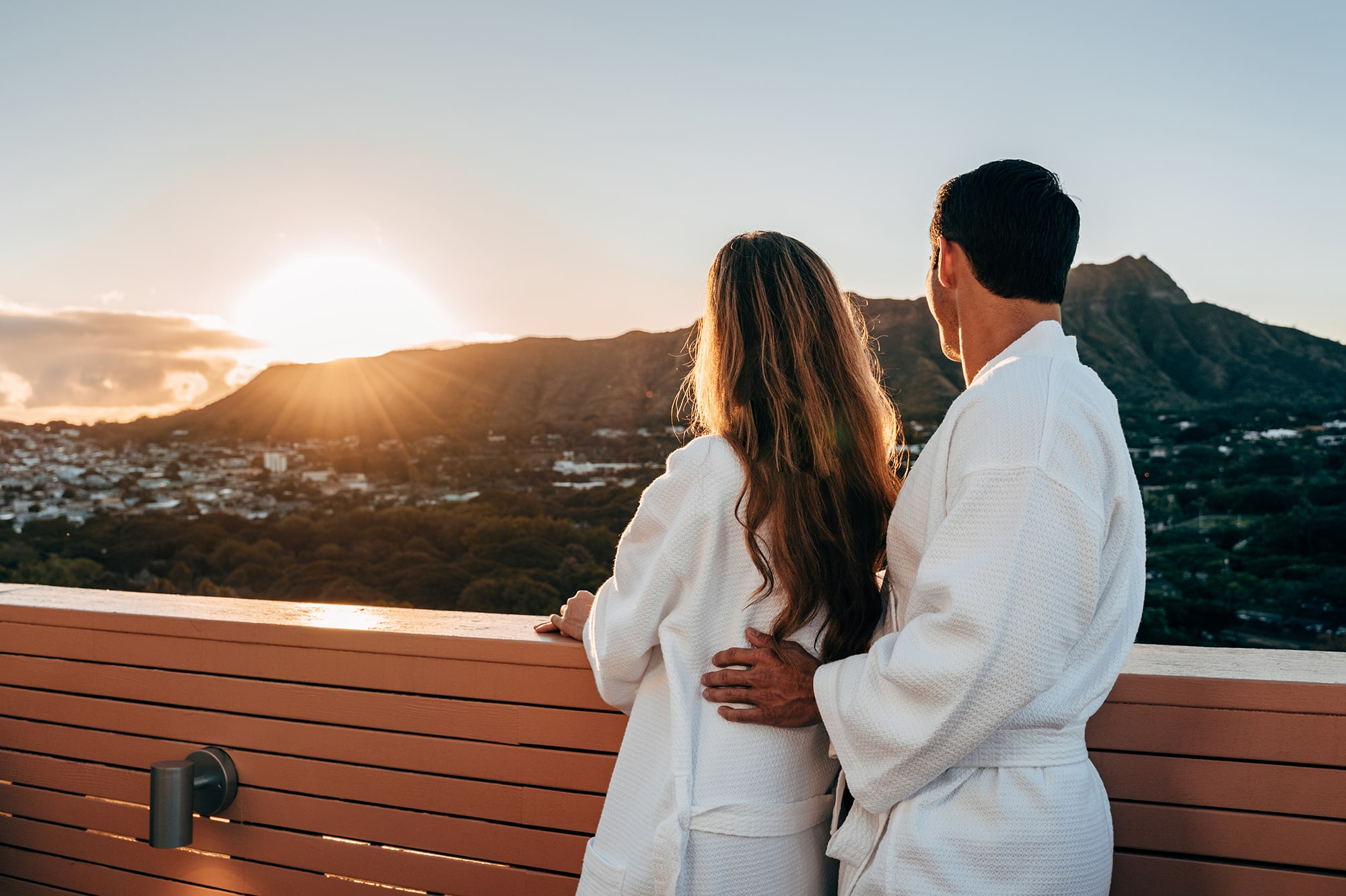 Couple in robes on balcony watching sunset